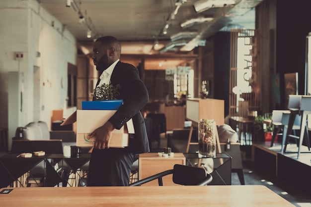 Responsabile nero leaves workplace with office box. Foto Premium