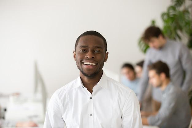 Responsabile professionale afroamericano felice che sorride esaminando macchina fotografica, ritratto di colpo in testa Foto Gratuite
