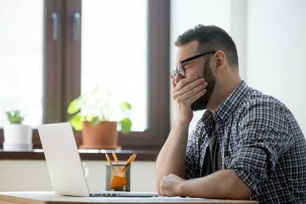 Responsabile sonnolento stanco in vetri che sbadigliano sul lavoro in ufficio Foto Gratuite