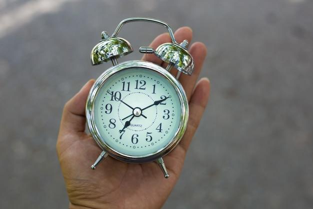 Restro classic alarm clock in a hand. il tempo è in esecuzione. Foto Premium