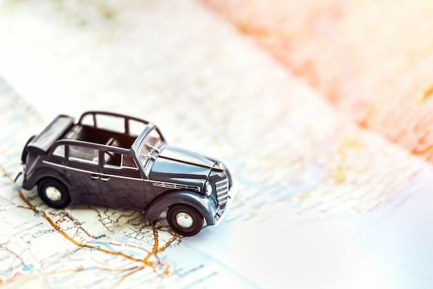 Retro automobile di cabrio del giocattolo sulla mappa, concetto di turismo Foto Premium