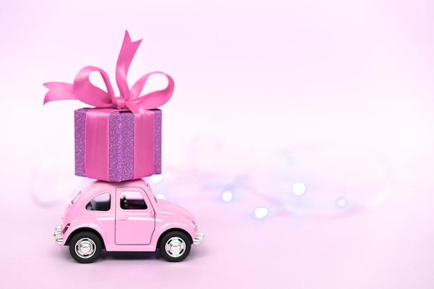 Retro automobile rosa del giocattolo che consegna il contenitore di regalo per il san valentino sul rosa Foto Premium