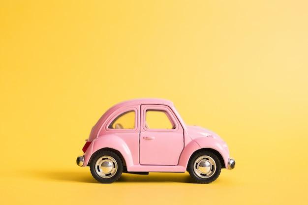 Retro automobile rosa del giocattolo su giallo. concetto di viaggio estivo taxi. Foto Premium