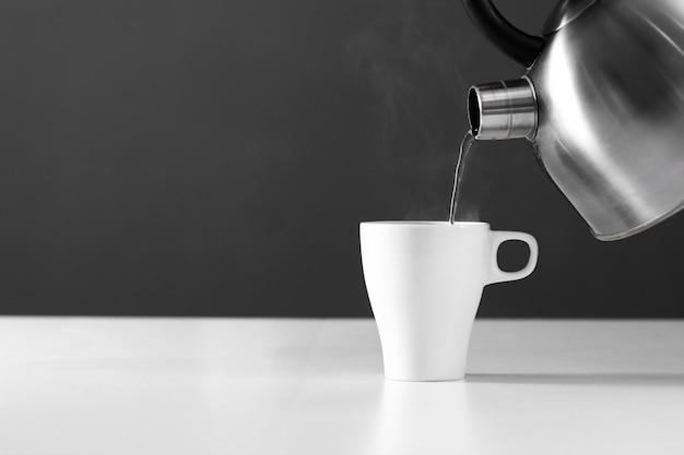 Retro bollitore che versa acqua in una tazza su un fondo scuro con fumo sulla tavola di legno Foto Premium