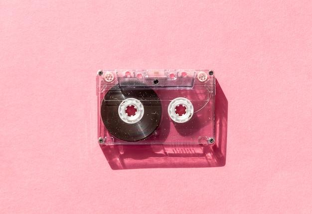 Retro cassetta audio trasparente trasparente su sfondo rosa. tecnologia musicale vintage Foto Premium