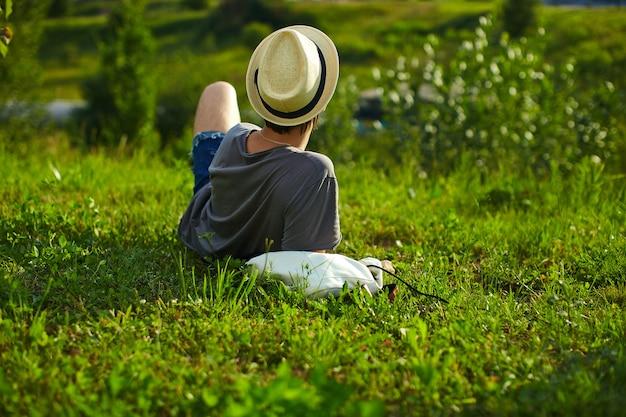 Retro del giovane attraente elegante uomo moderno in panno casual nel cappello con gli occhiali seduto nel parco in erba verde Foto Gratuite