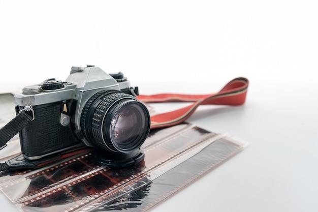 Retro macchina fotografica con cinturino rosso sul negativo del film Foto Premium