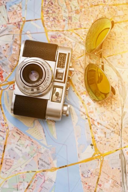 Retro macchina fotografica e occhiali da sole su una mappa Foto Gratuite