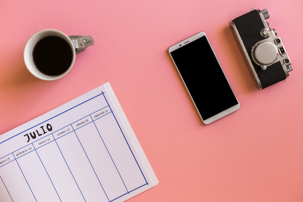 Retro macchina fotografica vicino a smartphone, tazza di bevanda e calendario Foto Gratuite