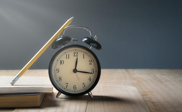 Retro sveglia, matita sulla tavola di legno con tempo del fondo di lerciume per il concetto del pranzo. Foto Premium