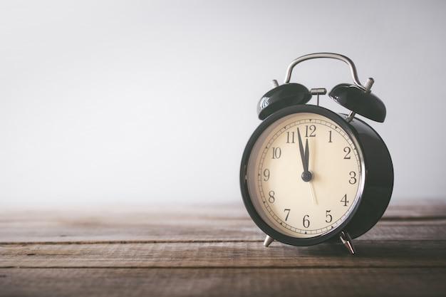 Retro sveglia sulla tavola di legno con tempo del fondo di lerciume per il concetto del pranzo. Foto Premium