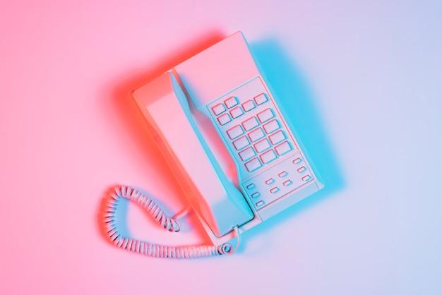 Retro telefono rosa con luce blu sulla superficie rosa Foto Gratuite