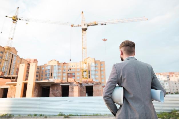 Retrovisione del modello maschio della tenuta dell'architetto e casco che esaminano cantiere Foto Gratuite