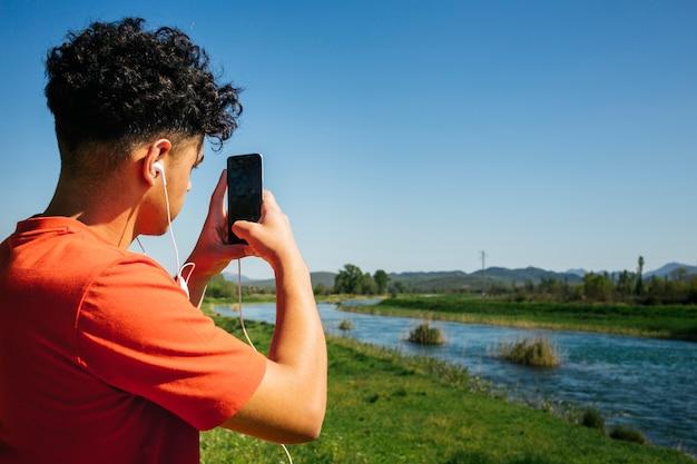 Retrovisione dell'uomo con il trasduttore auricolare che cattura maschera sullo smartphone Foto Gratuite