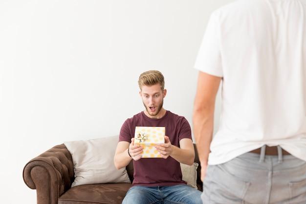 Retrovisione dell'uomo con l'uomo sorpreso che si siede sul sofà con il contenitore di regalo della tenuta Foto Gratuite