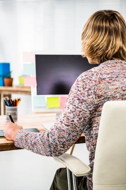 Retrovisione dell'uomo d'affari dei pantaloni a vita bassa facendo uso della grafica della compressa nel suo ufficio Foto Premium