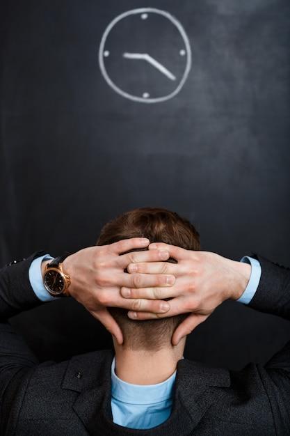 Retrovisione dell'uomo di affari che esamina le mani di orologio dietro il suo hea Foto Gratuite