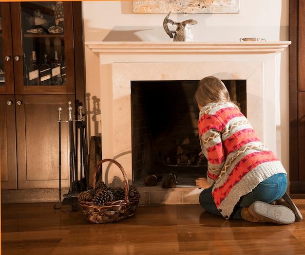 Retrovisione della donna che sistema legna da ardere nel camino a casa Foto Gratuite