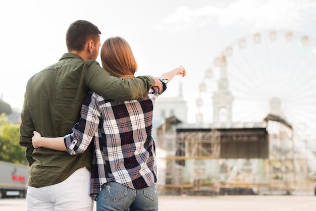 Retrovisione della donna con il suo ragazzo che indica alla ruota di ferris mentre Foto Gratuite