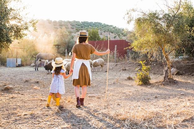 Retrovisione della donna con sua figlia che guarda gli animali nel campo Foto Gratuite
