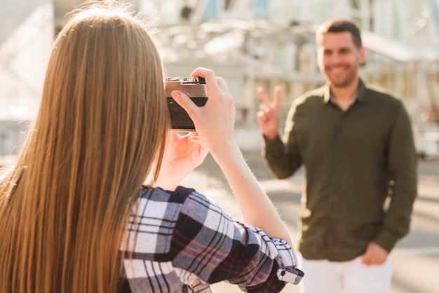 Retrovisione della donna dei capelli biondi che prende immagine dell'uomo con il gesto di pace Foto Gratuite