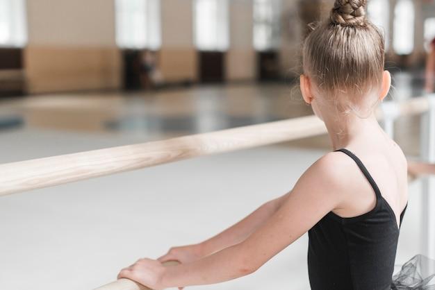 Retrovisione della ragazza della ballerina che tiene barra di legno Foto Gratuite