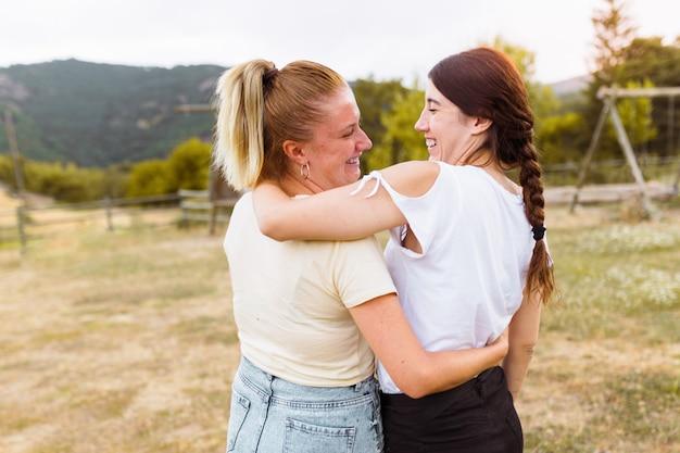 Retrovisione delle amiche che si sorridono e che si abbracciano nella campagna. concetto di migliore amico, amore e amicizia. Foto Premium