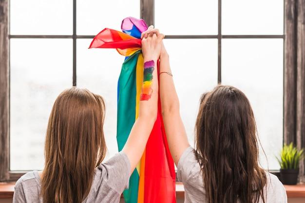 Retrovisione delle giovani coppie lesbiche che si tengono per mano e bandiera dell'arcobaleno che esamina finestra Foto Gratuite