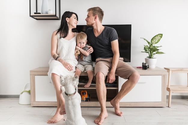 Retrovisione di un cane che esamina coppia che se lo guarda che si siede con il loro figlio davanti alla televisione Foto Gratuite