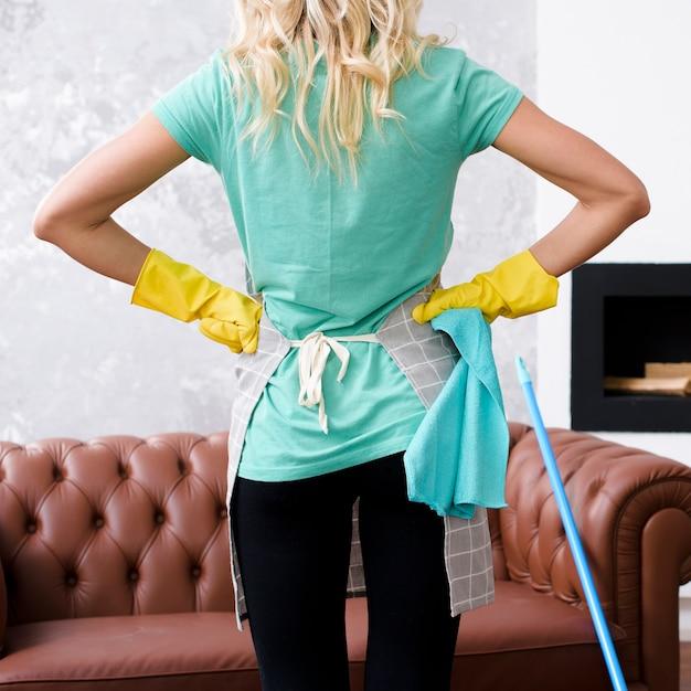 Retrovisione di un pulitore che indossa i guanti di gomma gialli che stanno con le sue mani sulle anche Foto Gratuite