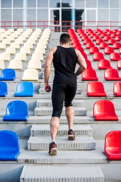 Retrovisione di un uomo che corre su per le scale sulla gradinata Foto Gratuite