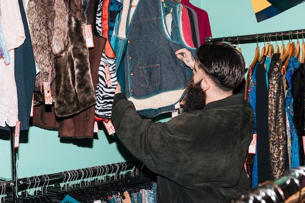 Retrovisione di un uomo che sceglie i vestiti che appendono sulla ferrovia nel negozio di vestiti Foto Gratuite