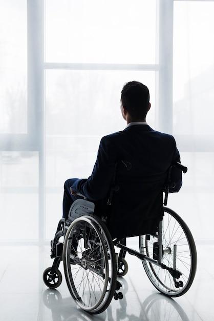 Retrovisione di un uomo d'affari in vestito che si siede sulla sedia a rotelle che esamina finestra Foto Gratuite