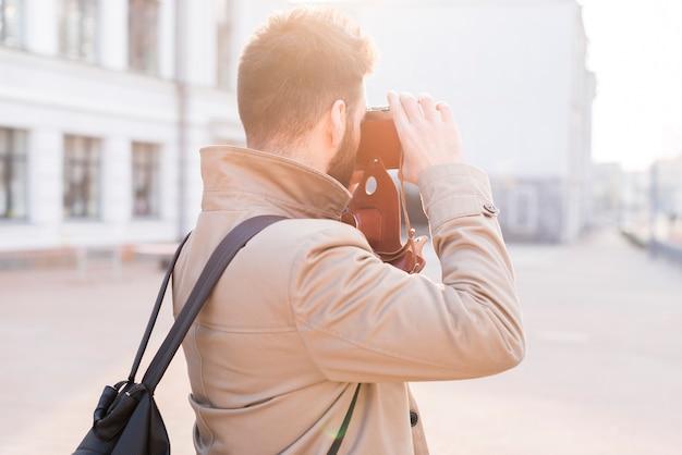 Retrovisione di un viaggiatore maschio che prende l'immagine nella città con la macchina fotografica Foto Gratuite