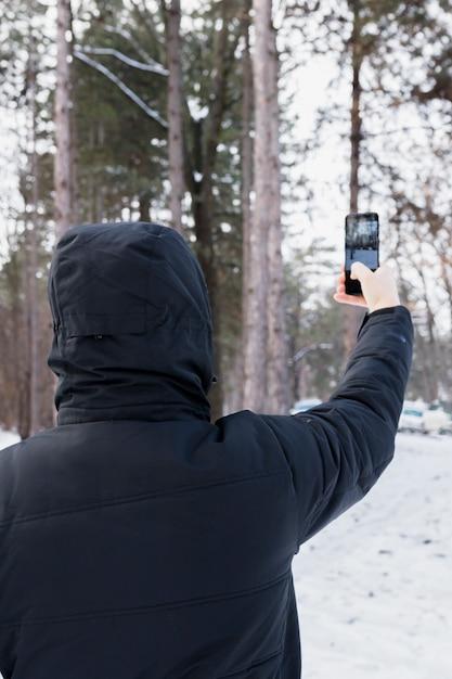 Retrovisione di una donna che prende fotografia in telefono cellulare Foto Gratuite