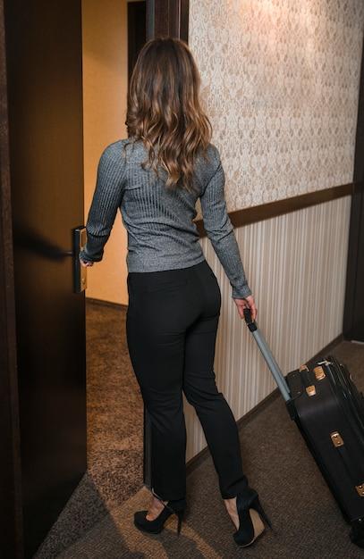 Retrovisione di una giovane donna bionda con la valigia che entra nella camera di albergo Foto Gratuite
