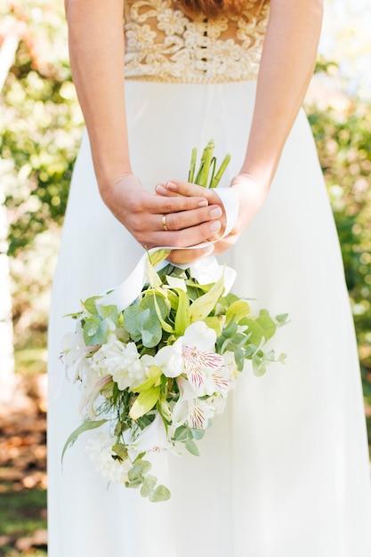Retrovisione di una sposa con la mano dietro lei indietro che tiene il mazzo del fiore Foto Gratuite