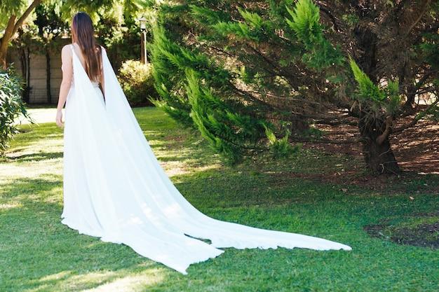 Retrovisione di una sposa in vestito lungo bianco che cammina nel parco Foto Gratuite