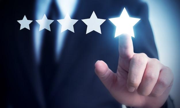 Revisione a cinque stelle commovente della mano dell'uomo d'affari per aumentare valutazione del concetto dell'azienda Foto Premium