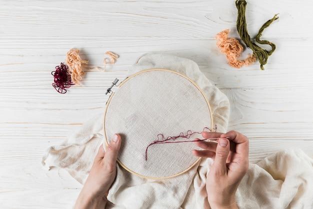 Ricamo con fili cucirini rossi su tessuto Foto Gratuite