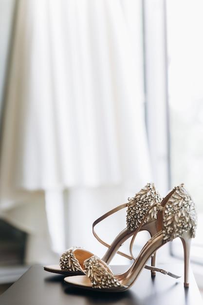 Ricche scarpe scintillanti con cristalli stanno davanti a un vestito appeso Foto Gratuite