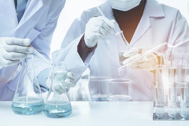 Ricercatore con provette chimiche da laboratorio in vetro con liquido per analisi Foto Premium
