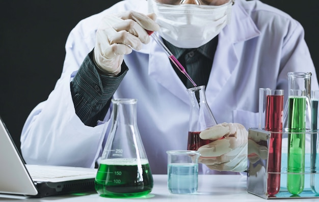 Ricercatore con provette chimiche di vetro da laboratorio con liquido Foto Premium