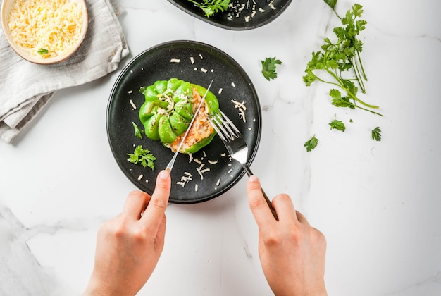 Ricette autunnali. la donna mangia peperoni ripieni fatti in casa con carne macinata, carote, pomodori, erbe, formaggio. sul tavolo di marmo bianco, in lamiera porzionata, mani nella foto, copia spazio vista dall'alto Foto Premium