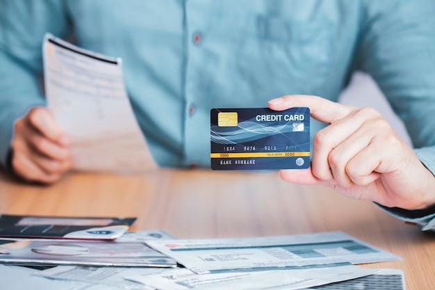 Ricevuta della fattura di pagamento dell'uomo d'affari con la carta di credito, commercio elettronico di affari per pagare concetto di debito della carta di credito Foto Premium