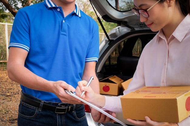 Ricevuta di firma della donna su carta dall'uomo di consegna per ottenere il suo pacchetto, concetto di consegna Foto Premium