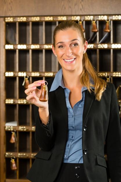 Ricezione dell'hotel, chiave della tenuta della donna a disposizione Foto Premium