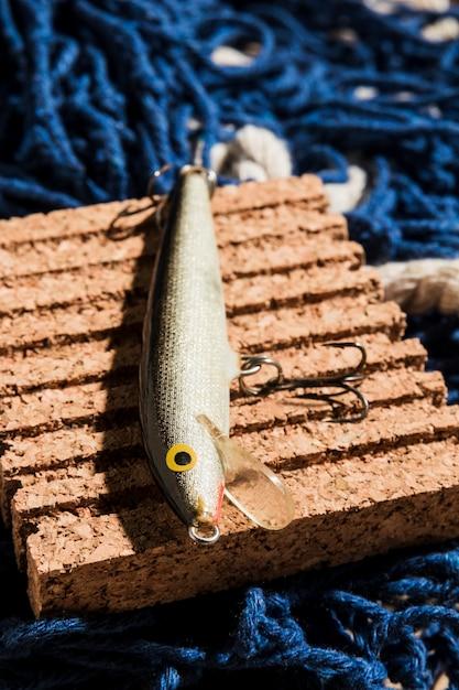 Richiamo di pesca sul pannello di sughero sopra la rete da pesca Foto Gratuite