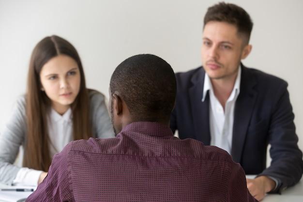 Richiedente africano che parla rispondendo domanda al colloquio di lavoro, retrovisione Foto Gratuite