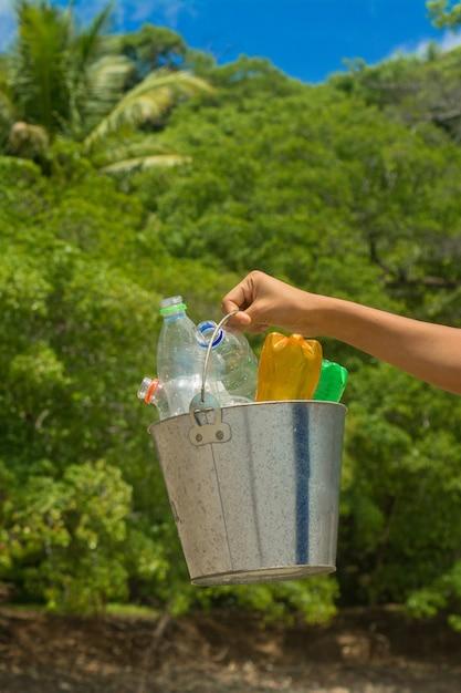 Riciclare, cestino con bottiglia di plastica in spiaggia Foto Premium